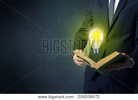 Businessman holding book with bulb.