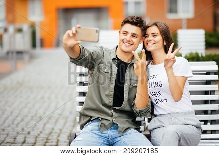 Happy Young Couple Hugging And Laughing Outdoors On The Bench With Victory Sign