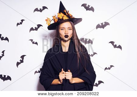 Halloween Party girl. Happy Halloween Sexy Witch with a black hat. Beautiful young woman in witches hat and costume Isolated on white background