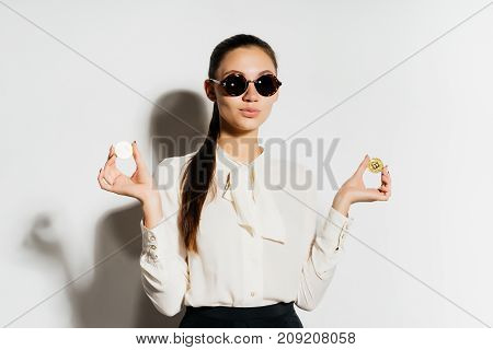 lovely long-haired girl with glasses is holding coins, isolated, bitcoins, crypto currency