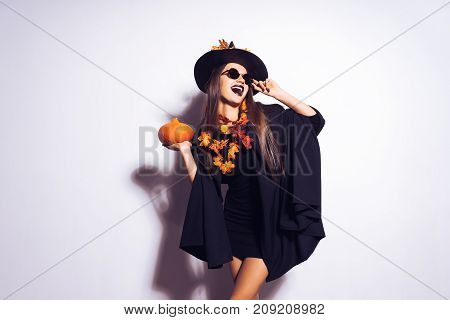 Beautiful mad halloween girl with long hair. A halloween woman in a black halloween dress and wearing a hat with orange leaves.