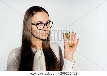 a beautiful long-haired girl with glasses is holding gold coins in her hands and looking into the camera. Bitcoins, crypto currency