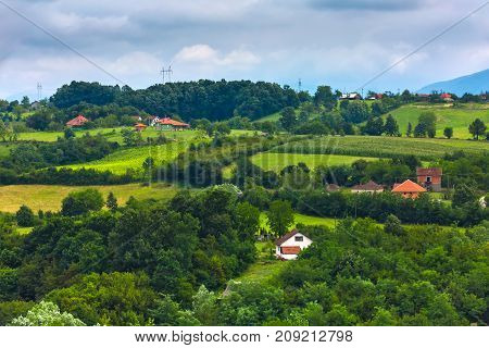 Rural houses on the fields and slopes in cloudy weather. Valley of Valjevo, Serbia.