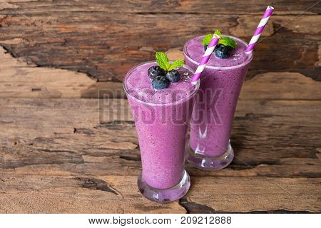 Blueberry smoothies and blueberry fruit yogurt for breakfast in the morning on a wooden floor.
