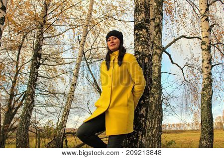 Autumn time: beautiful girl in a yellow coat posing against an autumnal birch forest.