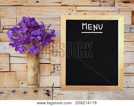 Violet vanda orchid in bamboo vase and blank menu board hanging on wooden plank wall. Shabby vintage interior style.