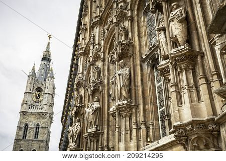 GHENT BELGIUM - JUNE 22 2016: Detail of the walls of the Town House full of ornaments along with the tower of Belfry of Ghent. Ghent Belgium.