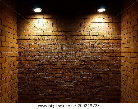abstract old brick wall in the dark with two spotlight warm light tone. brick wall in empty room. brick wall background for wallpaper