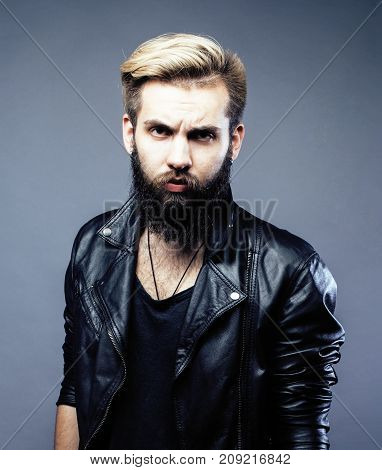 portrait of young bearded hipster guy on gray dark background close up, brutal modern man, lifestyle people concept close up