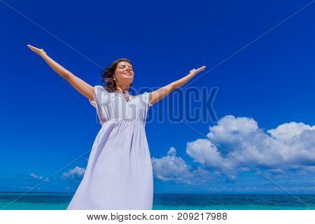 Woman in white dress posing in tropical sea beach with arms raised