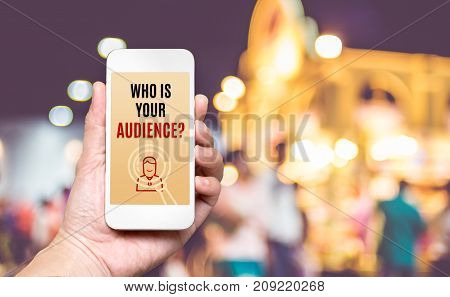 Hand Holding Mobile With Who Is Your Audience? Word On Screen With Blur Crowd Of People At Market Ba