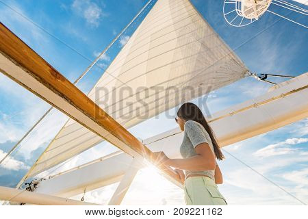 Luxury cruise ship vacation woman on yacht deck at sunset. Travel in Tahiti sail and mast on sky. Boat passenger sailing away on tropical getaway traveling in French Polynesia.