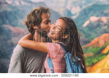 Couple in love kissing on nature travel hiking in mountains. Young hikers people happy together. Interracial backpacking lovers kiss portrait on vacation hike.