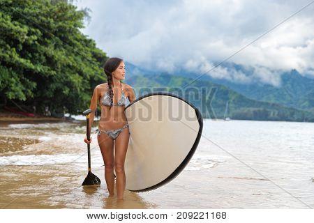 Stand up paddleboard bikini girl carrying paddle board going on ocean swim watersport activity at Puu Poa beach, Hanalei Bay, Kauai, Hawaii, USA. Hawaii travel fun swimwear Asian woman.