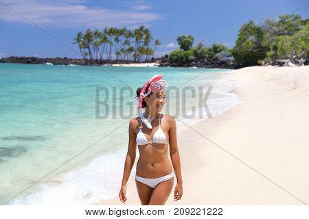 Hawaii beach vacation fun snorkel sport girl enjoying watersport activity going snorkeling with mask. Happy Asian woman in white bikini on summer travel holidays.