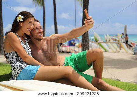 Selfie couple taking phone picture on Hawaii Waikiki beach travel vacation. Young people surfers lifestyle relaxing in Honolulu city after surf session with surfboards. Asian girl, Caucasian man.