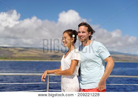 Cruise vacation happy couple relaxing on yacht in Hawaii. Young people having fun on scenic boat tour in Kauai, ocean tourism activity. Asian woman, Caucasian man.