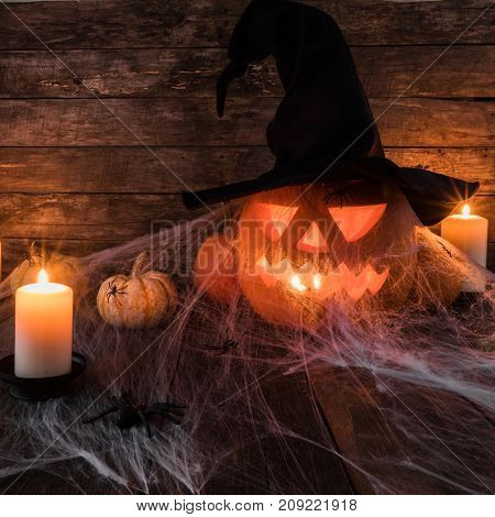 Jack O Lantern Halloween pumpkin with witches hat, spiders on web and burning candles