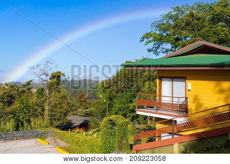 house with rainbow in a sunny day costa rica