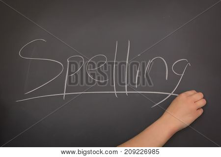 A Teacher writing the word Spelling on the blackboard