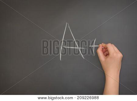Someone writing A plus on the blackboard
