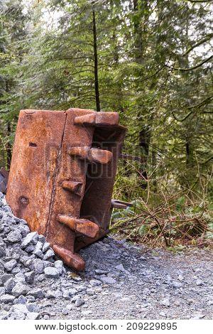 Rusty excavator bucket with broken tooth in the ground