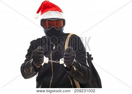 Arrested thief wearing mask and santa claus cap with handcuffs on isolated background