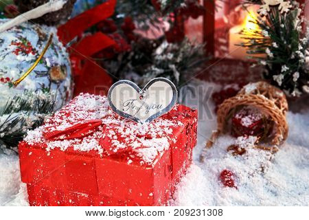 Christmas gift covered with snow in the light of a red lantern on the background of New Year's scenery