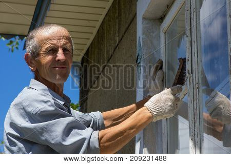 A portrait of a pensioner brushes the window from the old white paint