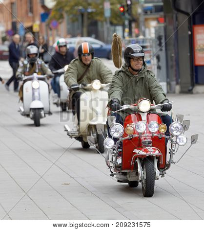 STOCKHOLM SWEDEN - SEPT 02 2017: Mods wearing old fashioned clothes from the 1960s driving retro vespa scooter at the Mods vs Rockers event at the Saint Eriks bridge Stockholm Sweden September 02 2017