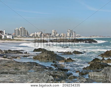 WINTER SEASCAPE, WITH HUGE BOULDERS IN THE FORE GROUND AND HIGH RISE BUILDINGS IN THE BACK GROUND 01jh