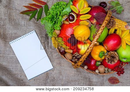 Autumn Composition: Wicker Basket With Fruits And Vegetables, Notebook, Top View.