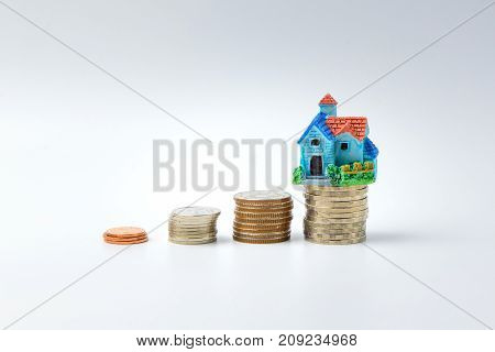 Concept for property ladder mortgage and real estate investment. house modell on top of coins stack.