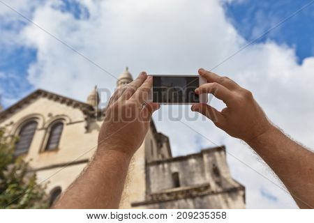 Tourist hands holding smart phone taking photo of Perigueux France