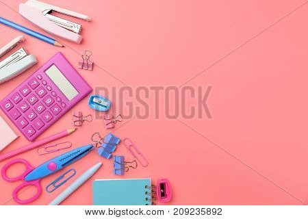 Stationary concept Flat Lay top view Photo of school supplies scissors pencils paper clipscalculatorsticky notestapler and notepad in pastel tone on pink background with copy space flat lay design.