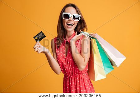 Close-up portrait of happy young brunette woman in sunglasses holding credit card and colorful shopping bags, looking at camera, isolated on yellow background