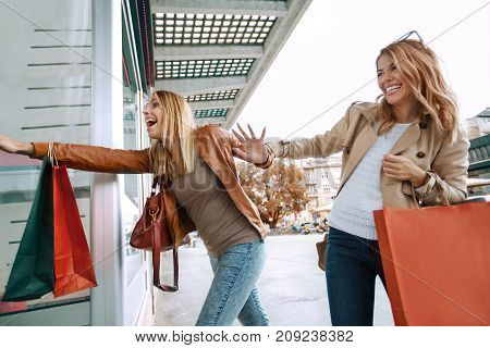 Black friday concept.Happy friends shopping. Two beautiful young women enjoying shopping in the city.
