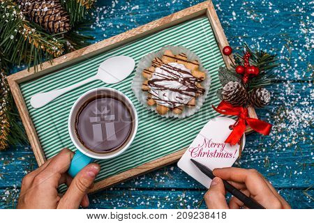 New Year's photo of tea with picture of gift, cake on table with spruce branch, person writing wishes on postcard
