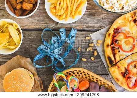 Fast food, tape measure on old wooden background. Concept of junk eating. Toned image. Top view.