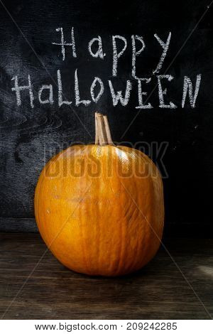 Halloween pumpkin on a black wooden background with the words chalk