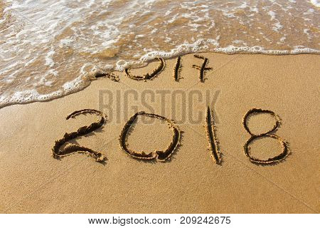 2017 and 2018 years written on sandy beach sea. Wave washes away 2017. Concept of 2017 is gone, come new year 2018.