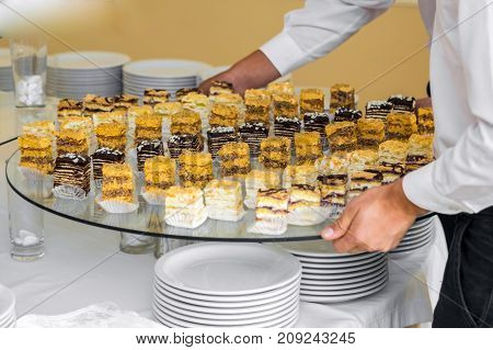 Waiters put on a buffet table a sweet pastry.
