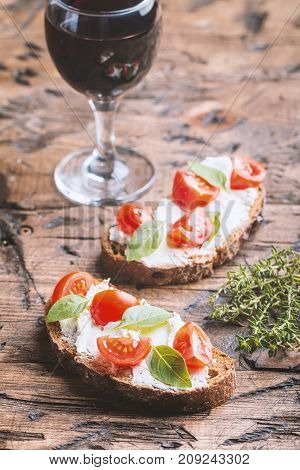 Close up of crostini appetizers with cherry tomatoes, basil, and cheese on wooden background
