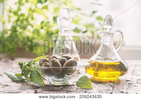 olive oil in glass bottle and olives over old wooden table