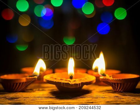 Happy Diwali - Diya lamps lit with bokeh background during diwali celebration.