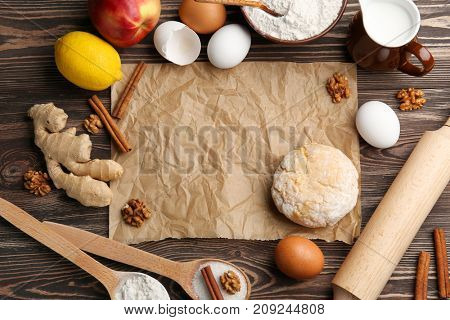 Parchment paper, raw dough and ingredients on kitchen table