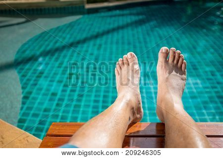 The foot of the men who sit near the pool in the resort at Pattaya. Thailand on weekend