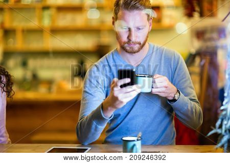 Young handsome man using mobile phone in coffee shop