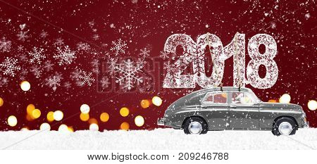 Santa Claus driving gray retro toy car delivering Christmas or New Year 2018 on festive red background
