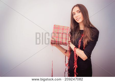 Happy brunette woman celebrating new year, holding christmas gift with red tinsel over light grey background